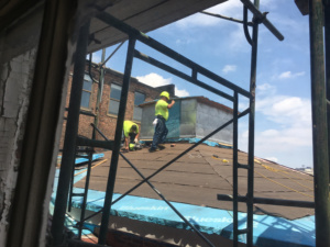 Two workers stand and work on the roof of the Peale building.